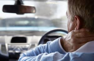 Close-up of male driver suffering from whiplash, pressing hand to his neck
