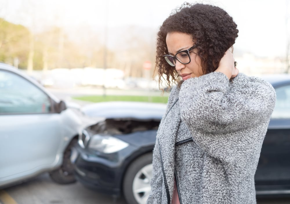 Woman holding the back of her neck, car crash in background